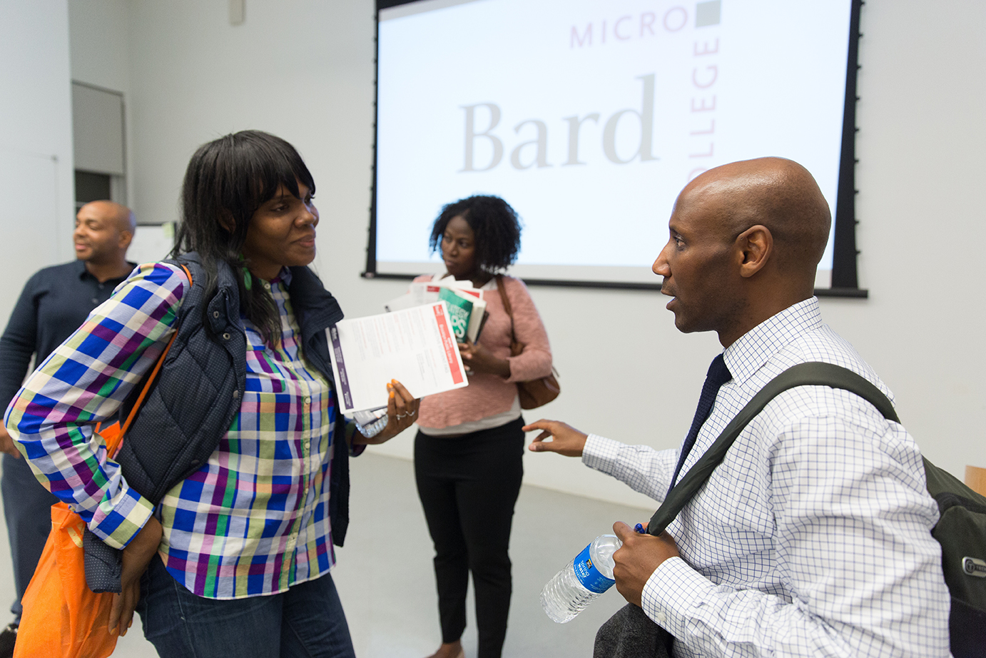 Female with papers talking to a man with a backpack on, with the Bard Microcollege logo projected onto a screen in the background.